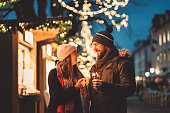 Young happy couple lighting up a sparkling stick. Women and men holding a sparkling stick at Christmas market, feeling the festive vibes, Christmas is almost here.