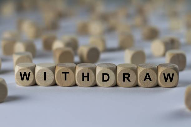 withdraw - cube with letters, sign with wooden cubes stock photo