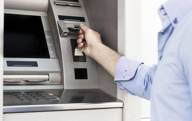 geld von einem geldautomaten abheben - bankkonto stock-fotos und bilder