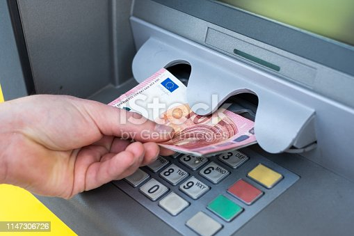 istock Withdrawing money from an atm bank machine 1147306726