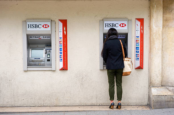 Withdrawing money Paris, France - July 28, 2015: A woman is withdrawing money from an ATM machine on a street in Paris in France. hsbc stock pictures, royalty-free photos & images