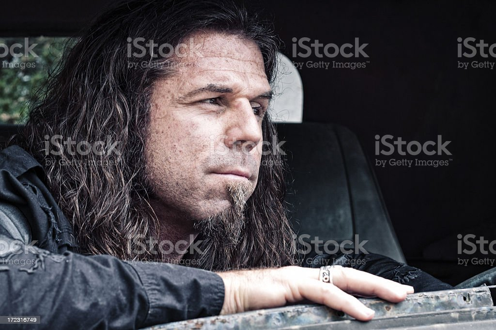 Withdrawn Man with Long Hair Inside Broken Down Car royalty-free stock photo