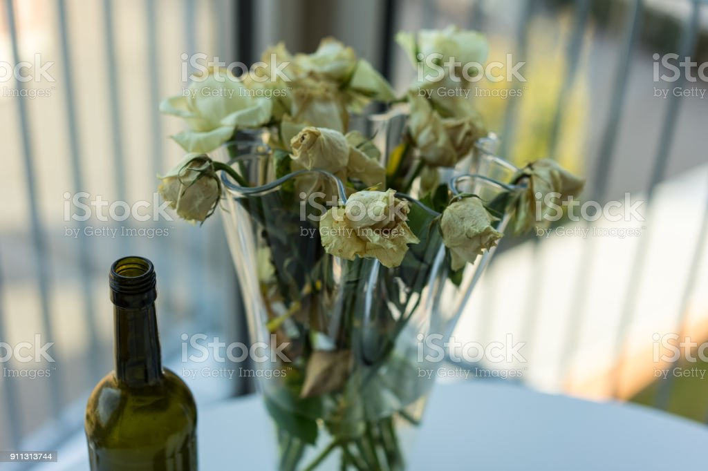 withered yellow roses and wine bottle stock photo