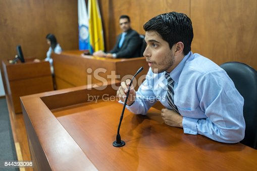 Portrait of a male witness addressing the courtroom in a trial - legal system concepts
