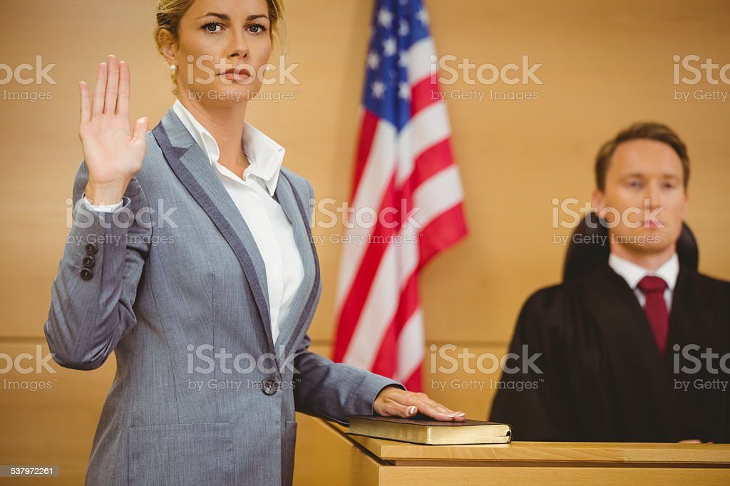 Witness swearing on bible telling the truth stock photo