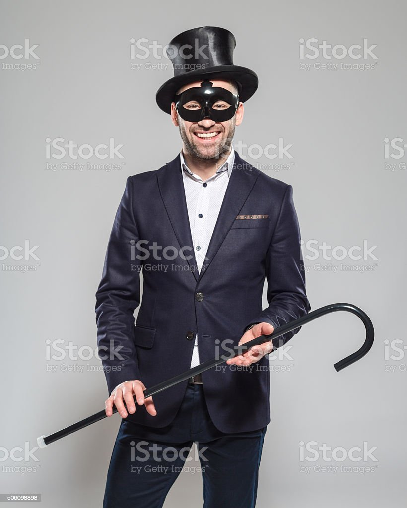 Wizard. Elegant bearded man wearing top hat and carnival mask Portrait of elegant bearded businessman wearing jacket, top hat and carnival mask. Standing against grey background, holding walking stick in hands and smiling at camera. Studio shot, one person.  Adult Stock Photo