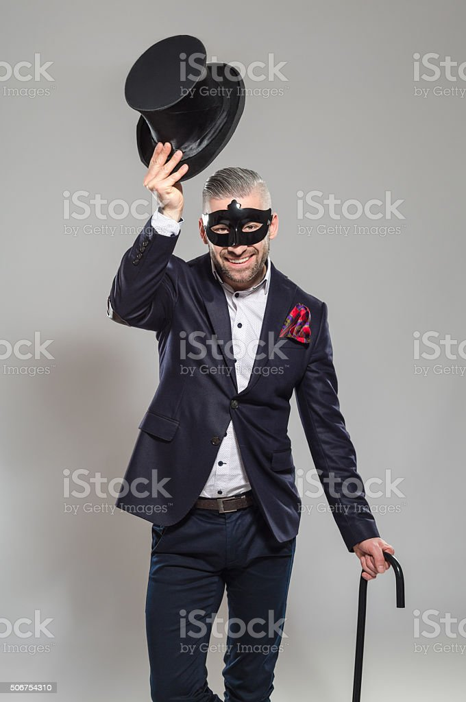 Wizard, elegant bearded man wearing top hat and carnival mask Portrait of elegant bearded businessman wearing jacket, top hat and carnival mask. Standing against grey background, holding walking stick in hand, raising his hat and smiling at camera. Studio shot, one person.  Adult Stock Photo