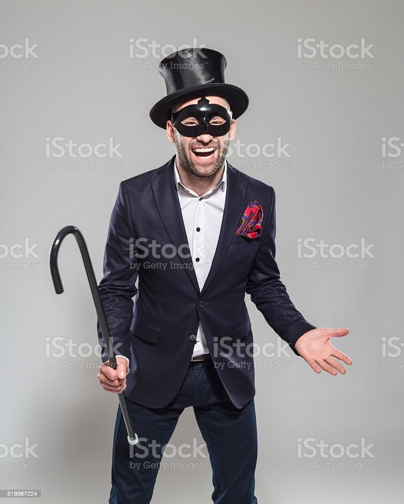 Wizard. Excited bearded man wearing top hat and carnival mask Portrait of elegant bearded businessman wearing jacket, top hat and carnival mask. Standing against grey background, holding walking stick in hands and laughing at camera. Studio shot, one person.  Adult Stock Photo