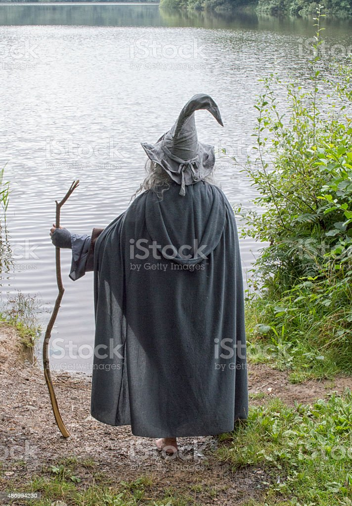 Wizard in a grey robe over looking a lake stock photo