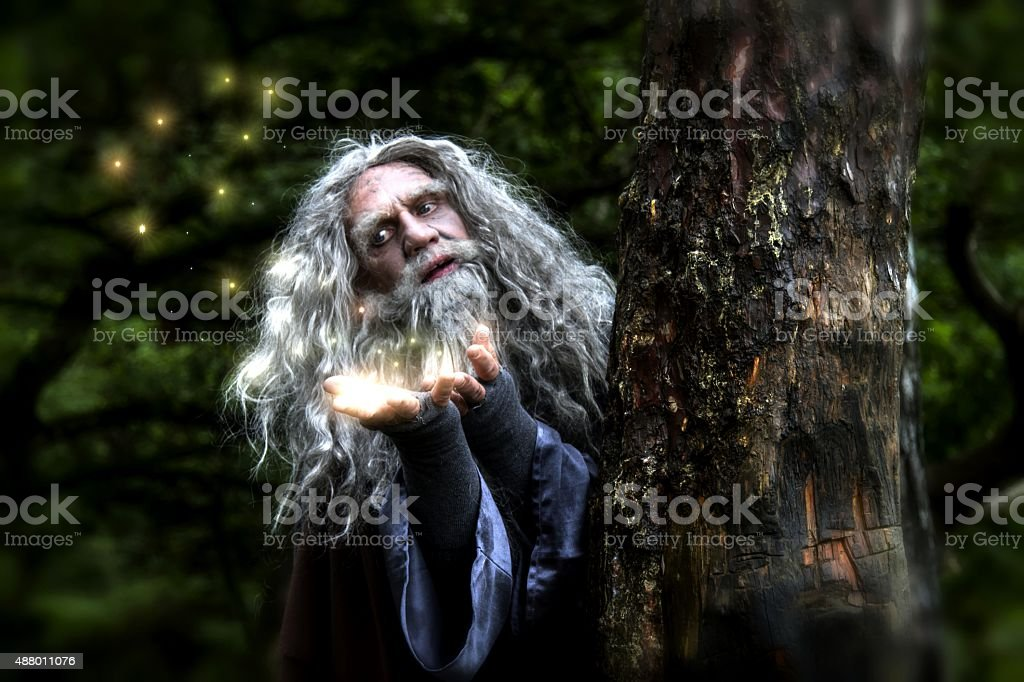 Wizard in woods creating lights stock photo