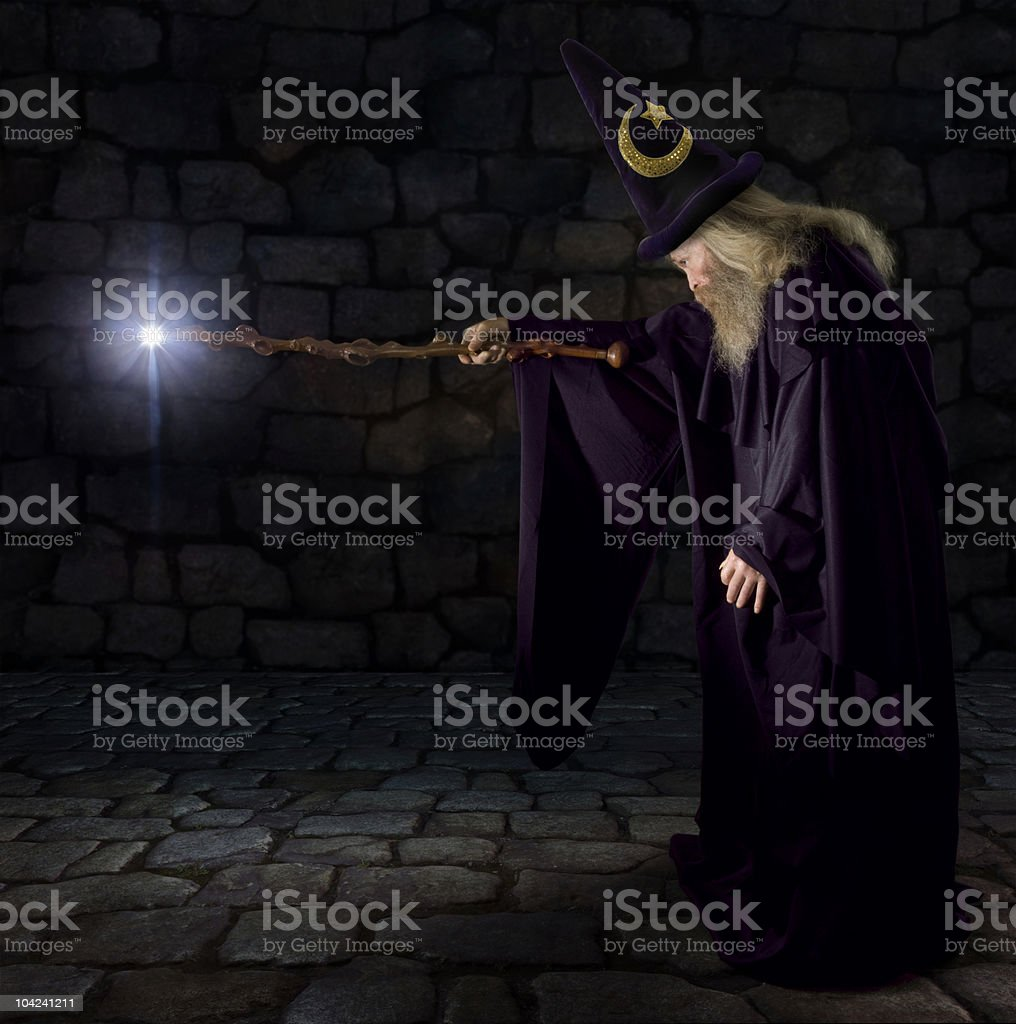 A wizard pointing his glowing wand stock photo
