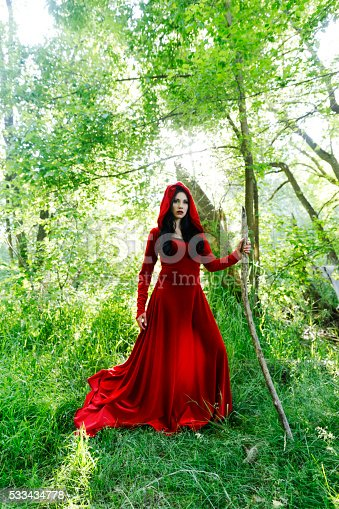 Woman in red hooded dress with thorn crown walking into the forrest.