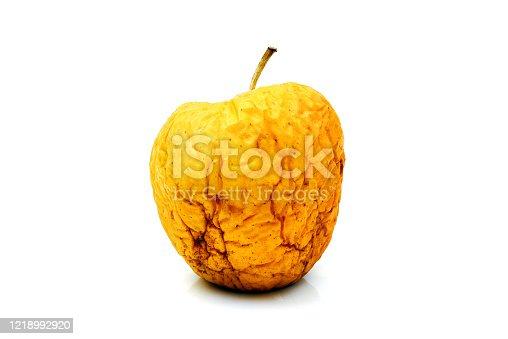 wizened wrinkled yellow apple isolated on white background