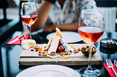 wo glasses of rose wine and board with fruits, bread and cheese on wooden table