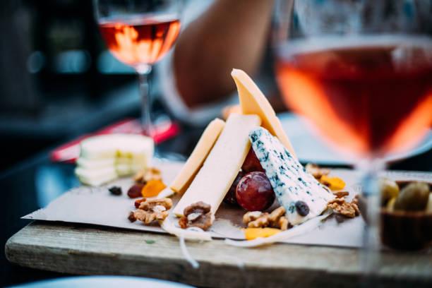 나무 테이블에 과일, 빵과 치즈와 장미 와인과 보드의 와이 안경 - 식전 반주 뉴스 사진 이미지