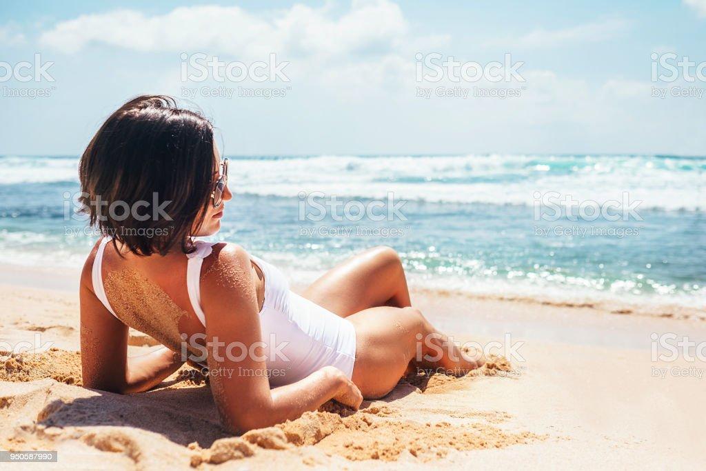 Woamn nimmt ein Sonnenbad am tropischen Strand – Foto