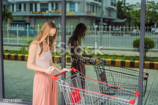 istock Woan hand disinfecting shopping cart with alcohol spray for corona virus or Covid-19 protection 1221373221