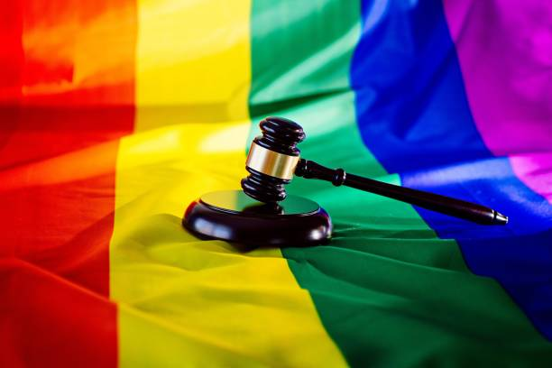 Woden judge mallet symbol of law and justice with lgbt flag Woden judge mallet symbol of law and justice with lgbt flag in rainbow colours. Lgbt rights and law courtyard stock pictures, royalty-free photos & images