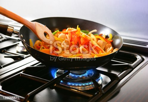 Wok cooking Stirfry vegetables and chicken on Gas flame.