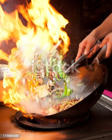 Cooking food on the wok and letting the oil catch flames to add a smokey flavour
