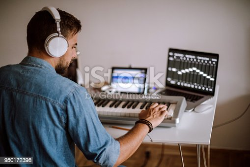 Young Musician Playing Synth And Writing New Composition