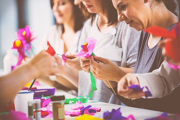 Wokshop for woman Group of women working on workshop, making coloful paper flowers. Close up of hands. blotter stock pictures, royalty-free photos & images