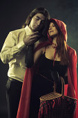 Brutal long-haired man holding hand of Red Riding Hood over dark background