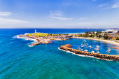 Aerial view of Wollongong city harbour with lighthouses and breakwater wall protecting marina and beaches.
