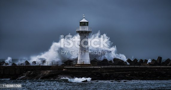 Wollongong Harbour, NSW, Australia - June 4: Wave breaking in a circular way behind the Breakwater Lighthouse of Wollongong during a storm, 16:9 aspect ratio
