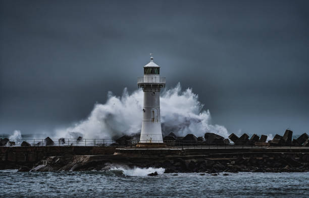 Wollongong Breakwater Lighthouse in the Storm The Breakwater Lighthouse of Wollongong with a wave breaking behind it during a storm groyne stock pictures, royalty-free photos & images