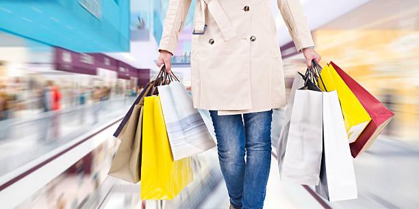 womam walking in shopping mall - shopaholic stockfoto's en -beelden