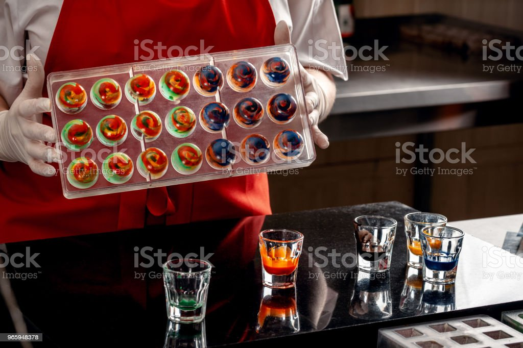 Woman a confectioner in red uniform and white gloves doing candy in special shapes from dairy chocolate with edible paint - Royalty-free Adulto Foto de stock