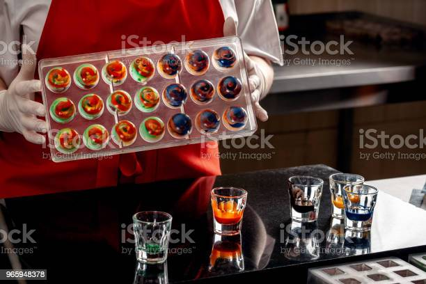 Woman A Confectioner In Red Uniform And White Gloves Doing Candy In Special Shapes From Dairy Chocolate With Edible Paint - Fotografias de stock e mais imagens de Adulto