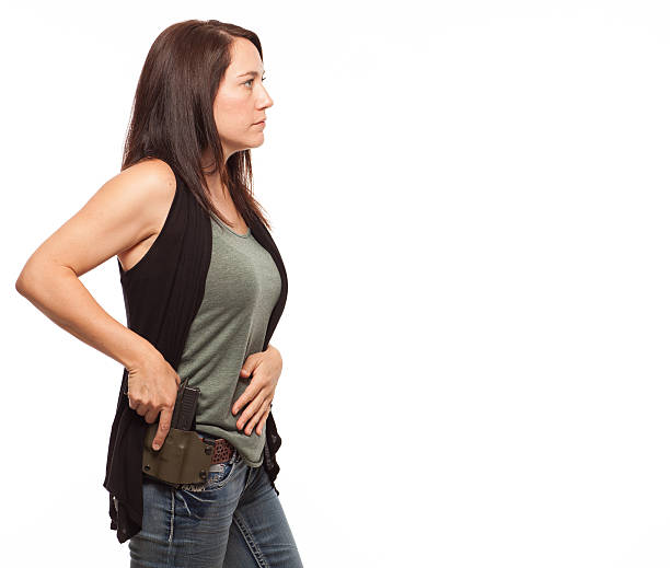 woman about to draw gun from holster with copy space. - 2015 stok fotoğraflar ve resimler