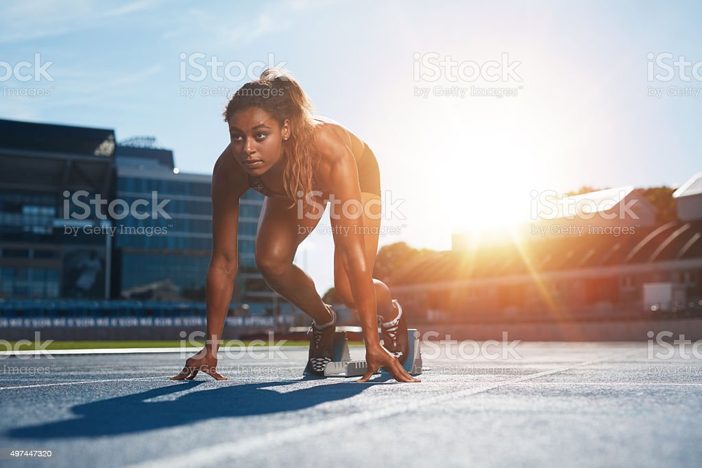 Woman about to start a sprint Confident female athlete in starting position ready for running. Young woman about to start a sprint looking away with bright sunlight from behind. 2015 Stock Photo
