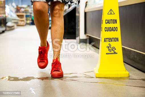 A female customer about to step into a puddle of water in a store.  There is a caution, wet floor sign beside the water.