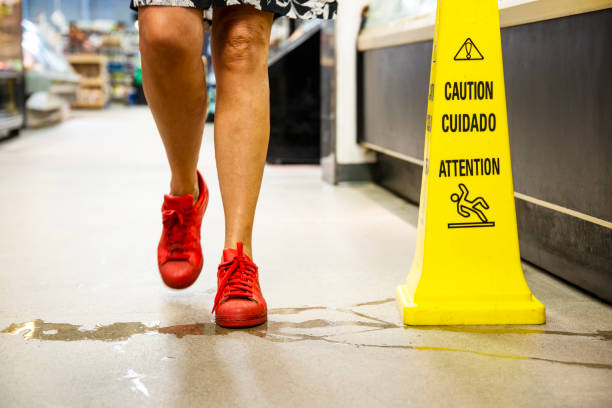A woman about to step into a puddle of water in a store stock photo