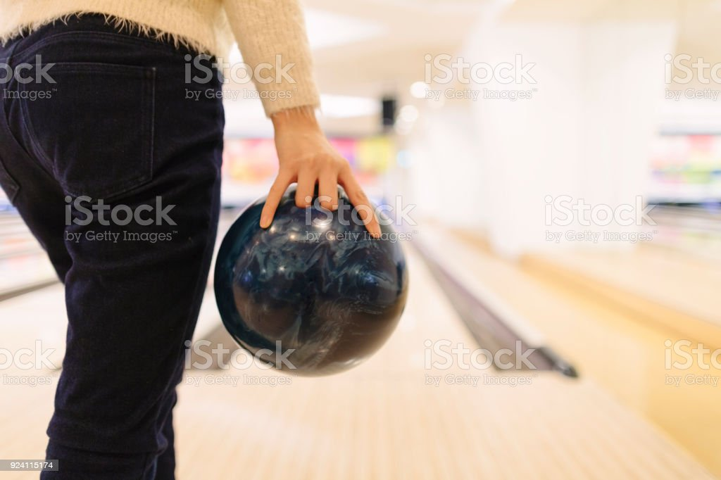 An unrecognizable woman is about to throw a bowling ball.