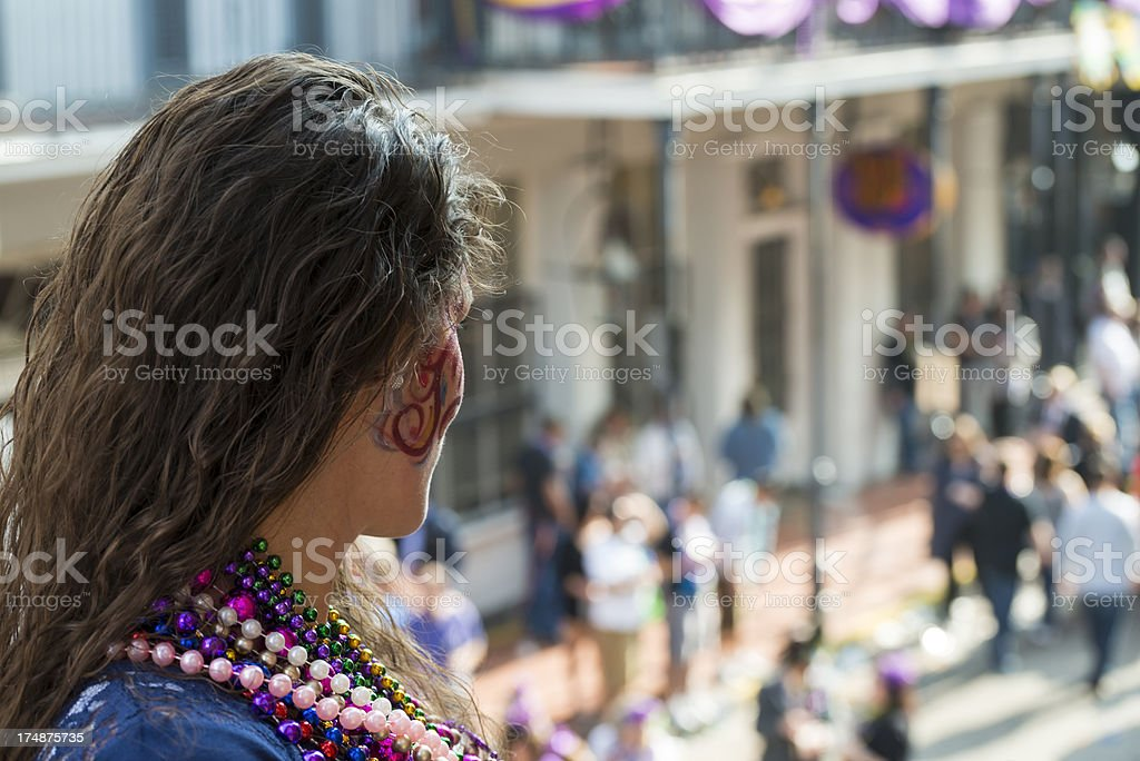 Woman above Bourbon Street looking at crowd during Mardi Gras stock photo