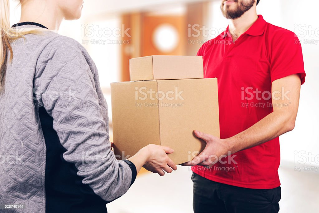 woman accepting a delivery of boxes from delivery service courier stock photo