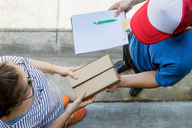 woman accepting on line shopping product from home delivery man ,top view scene stock photo