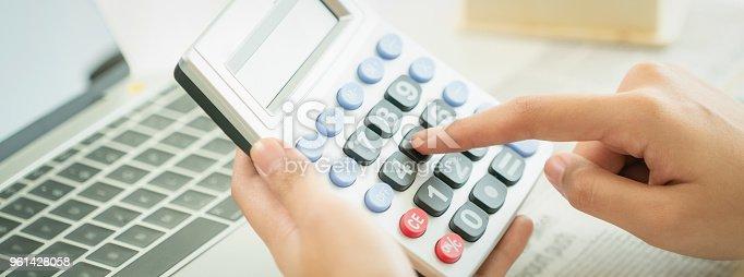 istock Woman accountant or bank worker uses calculator. 961428058