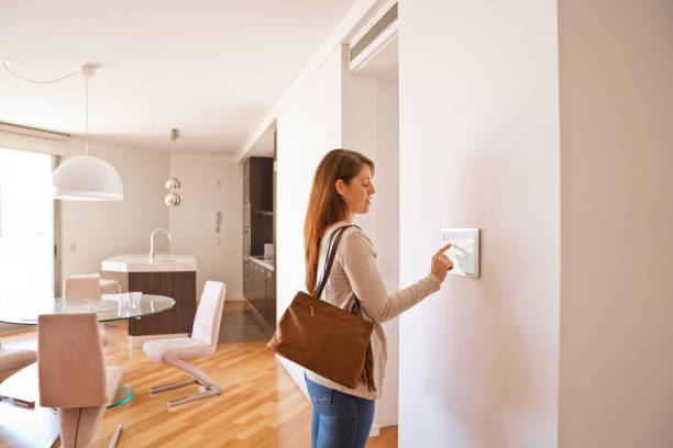 Woman activating smart home security system before leaving stock photo