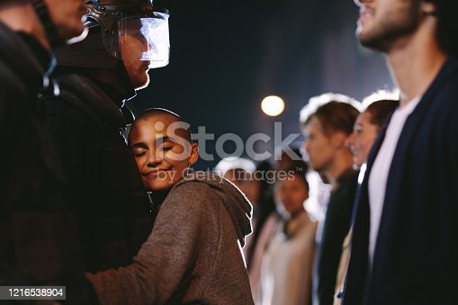 Woman hugging a policeman that patrol the street during the protests as a sign of peace. Woman embracing a security person during the demonstration.
