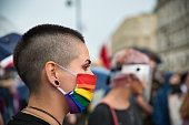 Warsaw, Poland, June 2020: LGBT supporters protesting on the street with rainbow flags. Portrait of woman activist with rainbow protective face mask