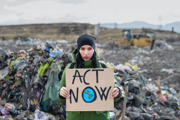 Woman activist with placard poster on landfill, environmental pollution concept. stock photo