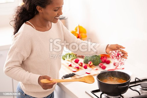 Housewife cooking vegetable soup, preparing food at the kitchen. Woman adding chopped radish to the boiling stock, holding spatula to taste bouillon.