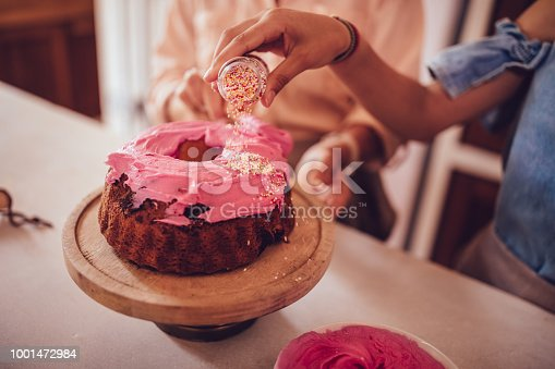 Girl decorating homemade cake with pink icing and colorful sprinkles while baking at home