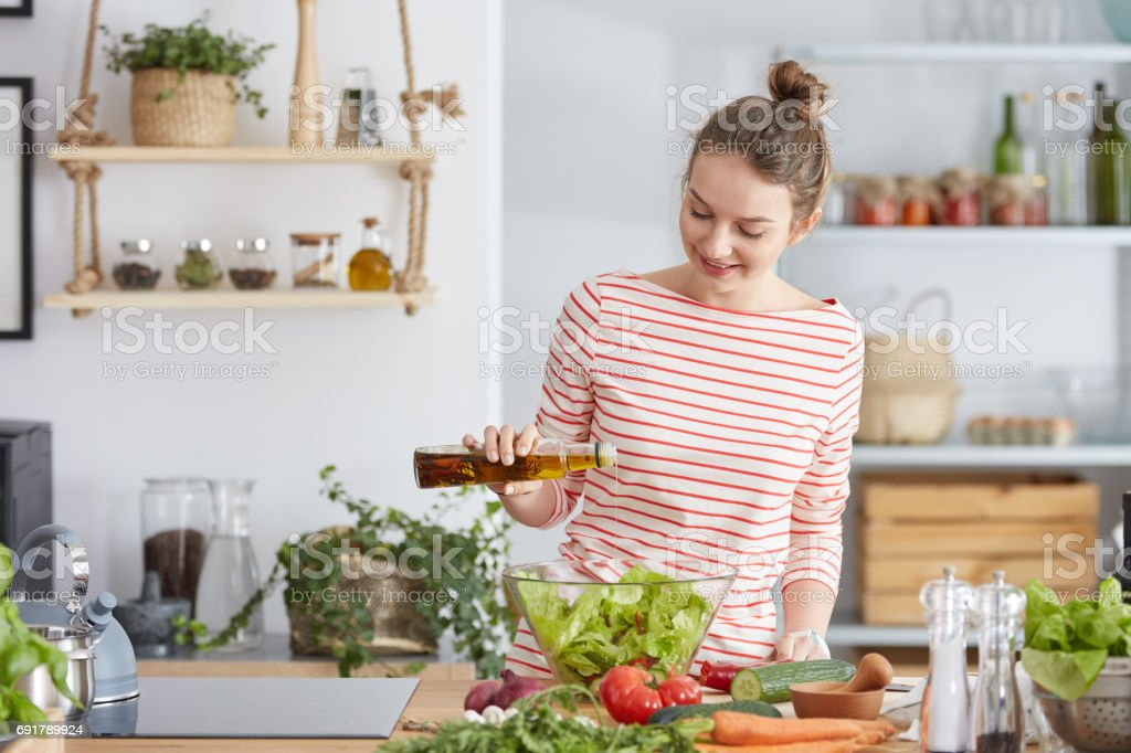 Woman adding olive to a salad stock photo