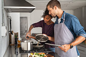 Young man in apron helping african woman to prepare lunch. Happy girl adding salt in pot for pasta while guy hold the lid up. Multiethnic couple cooking together with the help of a digital tablet for the recipe.